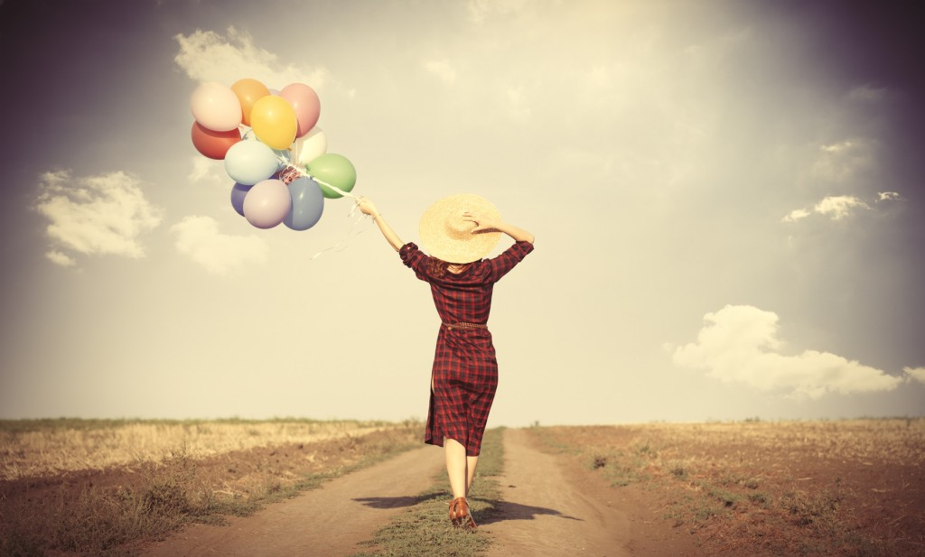 girl with multicolored balloons and bag